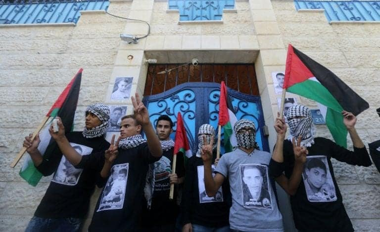Masked Palestinian youths pose in front of the UNDP (United Nations Development Programme) offices in Gaza City.